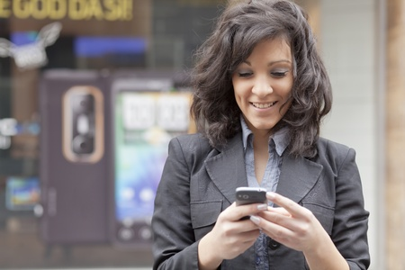woman smartphone: Young Woman with mobile phone walking background is blured city Stock Photo