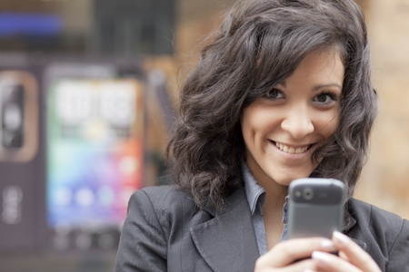 Young Woman with mobile phone walking background is blured city Stok Fotoğraf