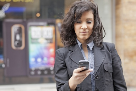 Woman with mobile phone walking background is blured city Stock Photo