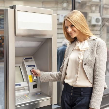 transaction: Jonge vrouw met behulp van Bank ATM geldautomaat op straat Stockfoto