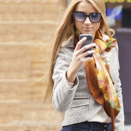 Junge Frau mit Smartphone-Walking auf der Straße, der Innenstadt. Im Hintergrund wird blured Straße Standard-Bild - 13078847