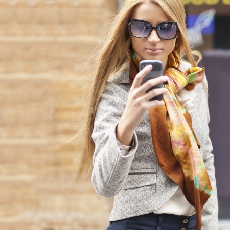 Young Woman with smartphone walking on street, downtown. In background is blured street photo