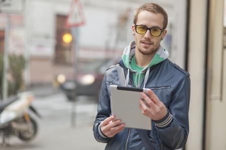 Junger Mann mit gelben Gläsern verwenden iPad Tablet-Computer auf der Straße, öffentlichen Raum. Unscharfen Hintergrund Standard-Bild - 13072496
