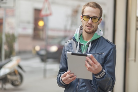 public space: Young man with yellow glasses use iPad tablet computer on street, public space. Blurred background