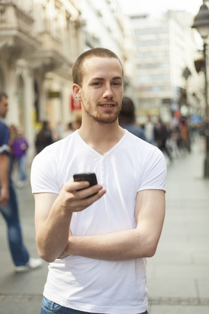 Junger Mann mit Handy Walking, ist Hintergrund Stadt blured Standard-Bild - 13134890