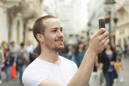 Man photographing with mobile phone walking, background is blured city Stok Fotoğraf