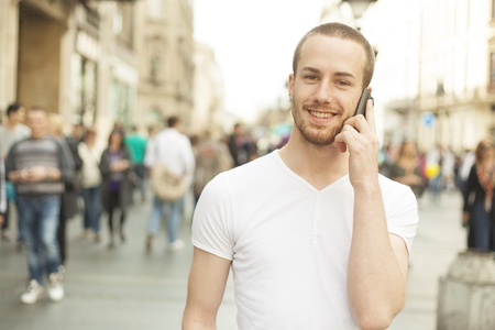 Young Man with mobile phone walking on street, background is blured city Stok Fotoğraf