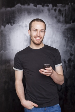 Smiling guy with smartphone typing SMS, studio shot on black background