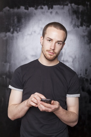 Smartphone in hands of young man, studio shot on black background photo