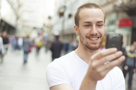 Young Man with mobile phone walking, background is blured city Stock Photo - 13226813