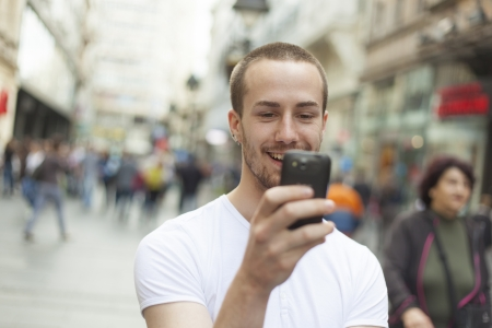 Young Man with mobile phone walking, background is blured city photo