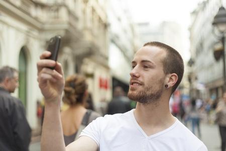 Man Fotograf mit mobila Telefon machen Foto auf der Straße Standard-Bild - 13247493