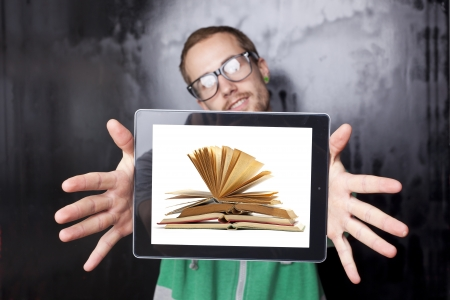 Good Looking Young Nerd Smart Guy Man Using Tablet Computer with book on screen photo