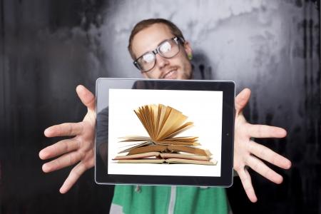 Gut aussehende junge Sonderling Smart Guy Mann mit dem Tablet-Computer mit Buch auf dem Bildschirm Standard-Bild - 14002538
