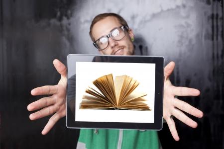 Junge Sonderling Smart Guy Mann mit dem Tablet-Computer mit Buch auf dem Bildschirm Standard-Bild - 14002522