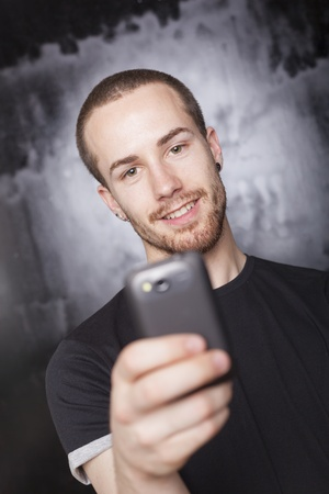 Smiling Man with smartphone, studio shot on black background Stock Photo - 14002604