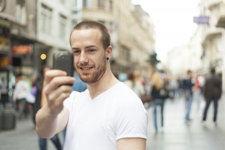 blured: Men on street photographing with mobile phone, background is blured city
