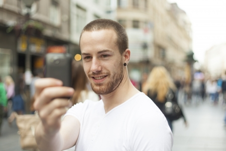 Guy on street photographing with mobile phone, background is blured city
