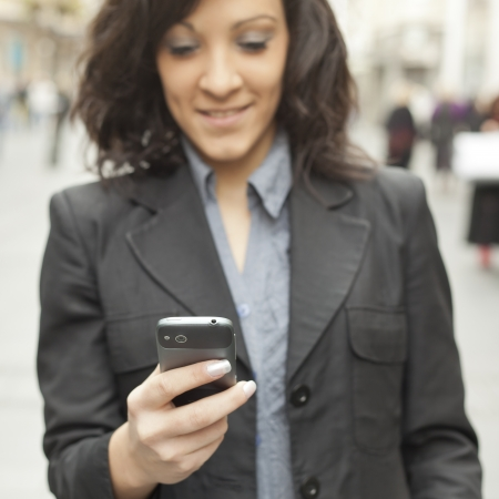 Young Woman with smartphone walking on street, downtown. In background is blured street. Phone in focus photo