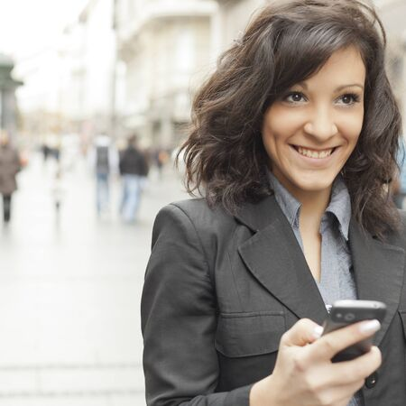 Young Woman with smartphone walking on street, downtown. In background is blured street, looking in front  photo