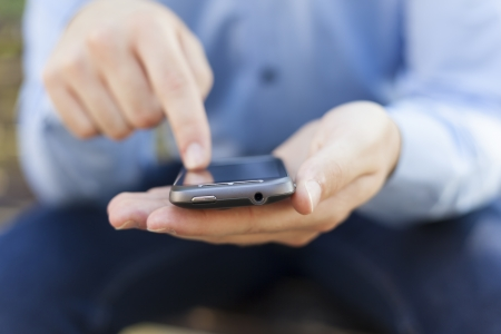 Man with smart phone on hand, blurred background Stock Photo - 14620345