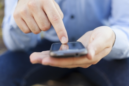 Man with smart phone on hand, blurred background Stock Photo - 14620350