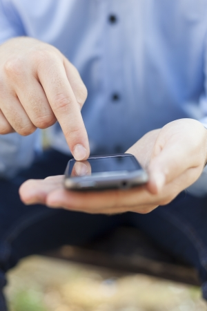 Man with smart phone on hand, blurred background Stock Photo - 14620349