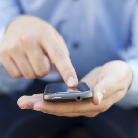 Man with smart phone on hand, blurred background Stock Photo - 14620340