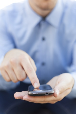 Man with smart phone on hand, blurred background Stock Photo - 14620343
