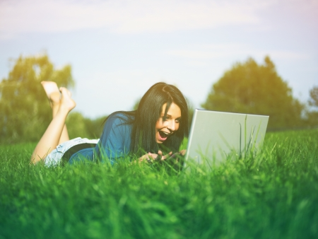 Young woman using laptop in park Stock Photo - 14932838
