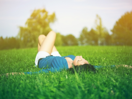 Young woman relaxing in park on green grass photo