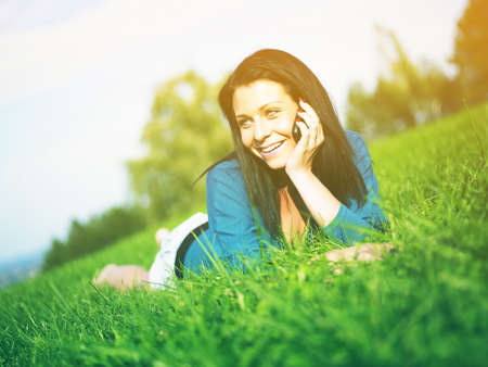 Young woman relaxing in park and telephoning Stock Photo - 14932849