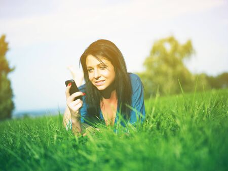 Young woman using mobile phone in park Stock Photo - 14932833
