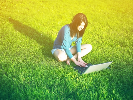 Young woman using laptop in park Stock Photo - 14932898