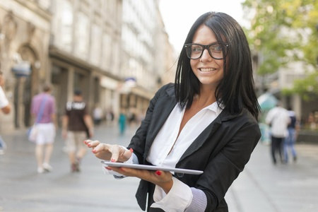 formal clothing: Beautiful Woman Using Tablet Computer on street, urban scene, formal clothing