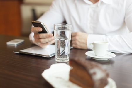Coffee break with tablet and smartphones, glass of wather in focus