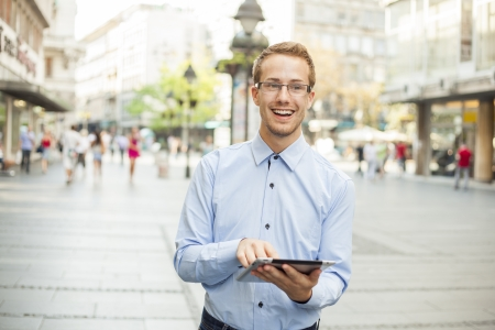 Goodlooking businessman with tablet computer on urban street Stock Photo - 17456069