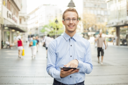 Young businessman with glasses and tablet computer on street photo