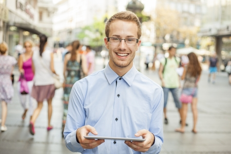 Young businessman using tablet computer in public space, group of people Stock Photo - 17456079