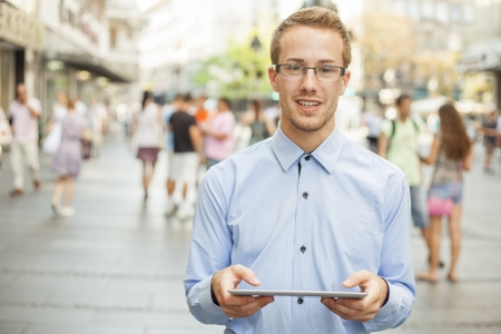 Modern Businessman in public - blured group of people in background Stock Photo - 17456072