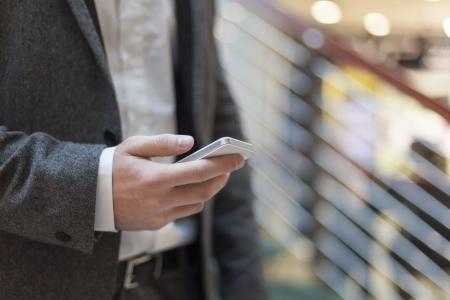 Man with smart phone auf der Hand, unscharfen Hintergrund, Business Gebäudeinnere Standard-Bild - 18398780