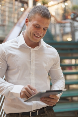 Businessman with tablet computer in hands, blurred background, modern business building Stock Photo