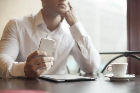wijzerplaat: Man met slimme telefoon bij de hand, wazig achtergrond