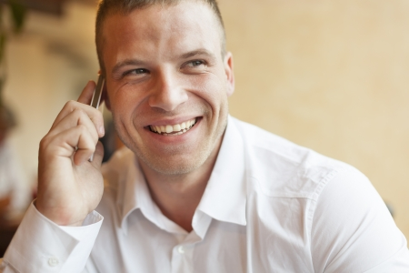 Men with smart phone speaking, blurred background, business building interior photo