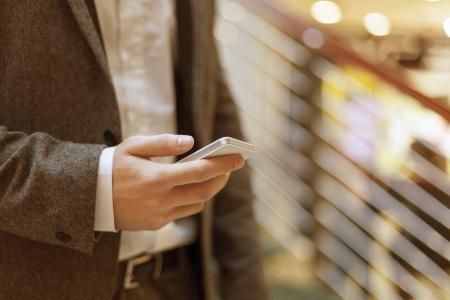 Smartphone in der Hand of businessman, verschwommenes hintergund, geschäfts building interior Standard-Bild - 18615617