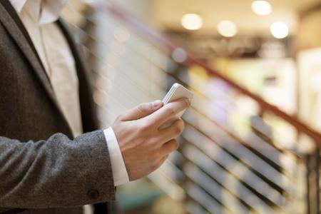 Smartphone in der Hand des Geschäftsmannes, unscharfen Hintergrund, Business Gebäudeinnere Standard-Bild - 18615615