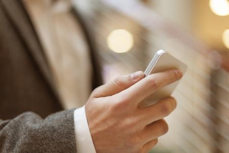 Smartphone in der Hand des Gesch?ftsmannes, unscharfen Hintergrund, Business Geb?udeinnere Standard-Bild - 18615616