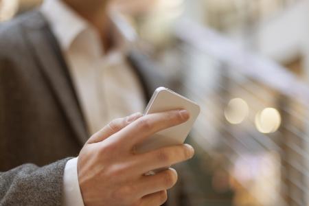 Smartphone in der Hand of businessman, verschwommenes hintergund, geschäfts building interior Standard-Bild - 18615614