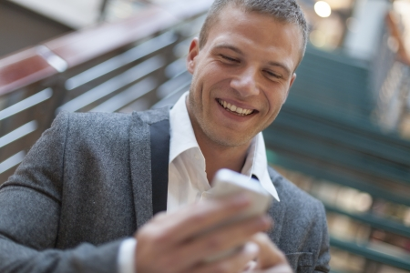 Good news! Men read sms on smartphone, blurred background, business building interior