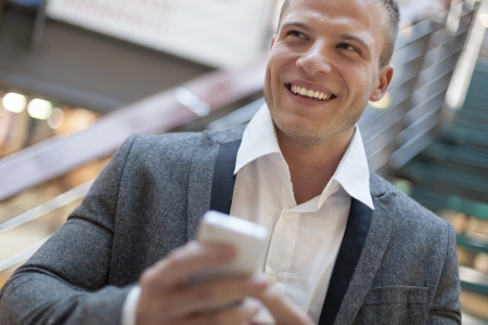 Men with smart phone on hand, blurred background, business building interior